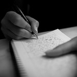 Photo of a person writing in a notebook.