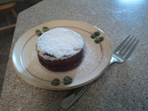 Photo of a small chocolate cake with powdered sugar topping.