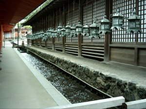 Photo of the side of a shrine with a trough of water looping the building and dozens of Japanese metal lanterns hung by the building.