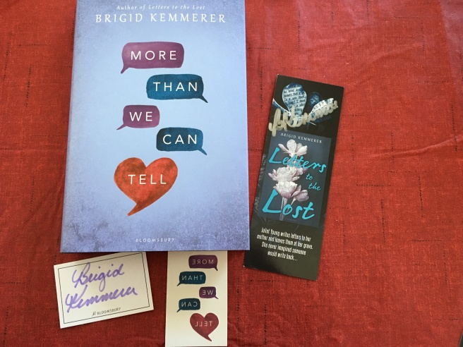 Brigid Kemmerer's More than We Can Tell, next to an autographed bookmark, an autographed sticker, and temporary tattoos that resemble the cover of the book.